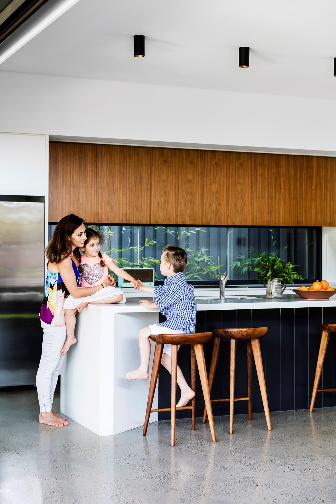 "The kitchen in this [1940s bungalow](https://www.homestolove.com.au/1940s-facade-hides-a-sizzling-21st-century-home-3269|target=""_blank"") features a black island bench and cabinetry. The overall look is fresh, with timber overhead cabinets, and a window splashback for plenty of natural light. *Photo: Maree Homer*"