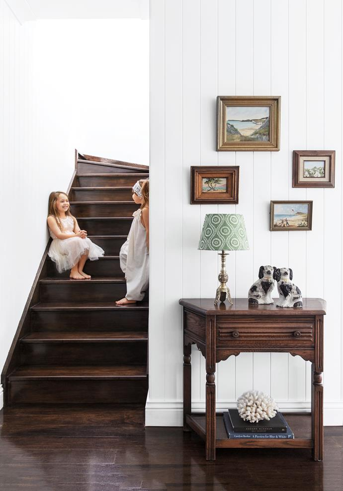 """Evie and Georgia love having Grandma just a staircase away. Paintings by RW McGivern (top), Grace Edwards (centre left) and anonymous artists. Lamp and hall table, both [Oliveaux Interiors](http://www.oliveaux.com.au/