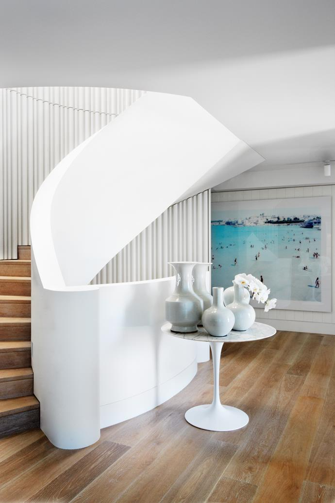 """The sinuous sweeping stair is the focal point of the house. Knoll Saarinen table holds white vessels from [Orient House](http://www.orienthouse.com.au/ target=""""_blank""""). Artwork by Massimo Vitali."""