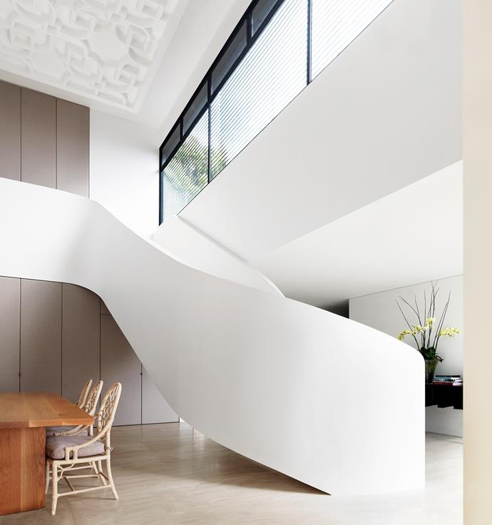 A curved staircase sweeps up into the void which features a custom-made plaster-relief ceiling.