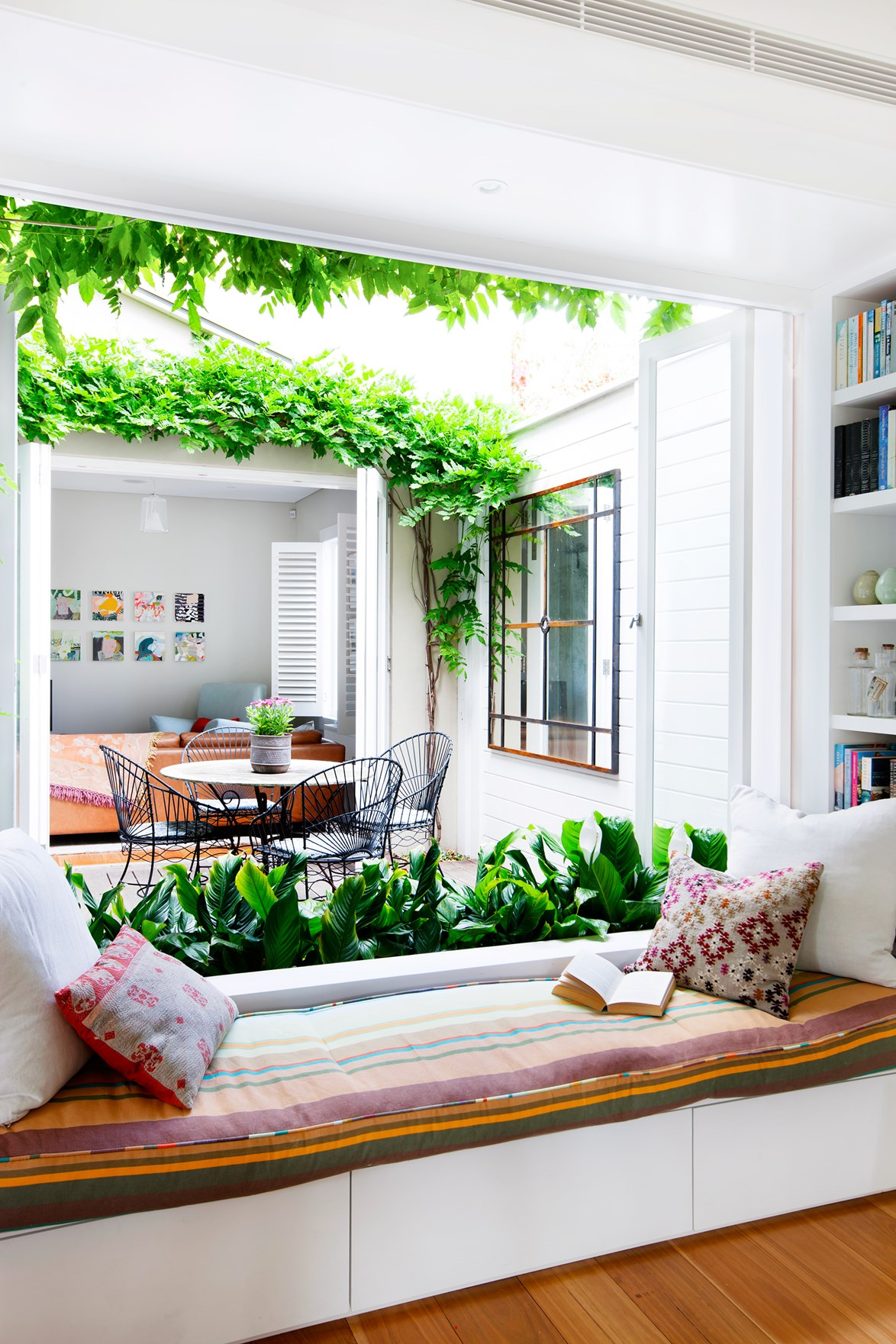 """This breezy window seats overlooks the central courtyard of this [Sydney semi](https://www.homestolove.com.au/sydney-semi-opens-up-to-the-elements-3388