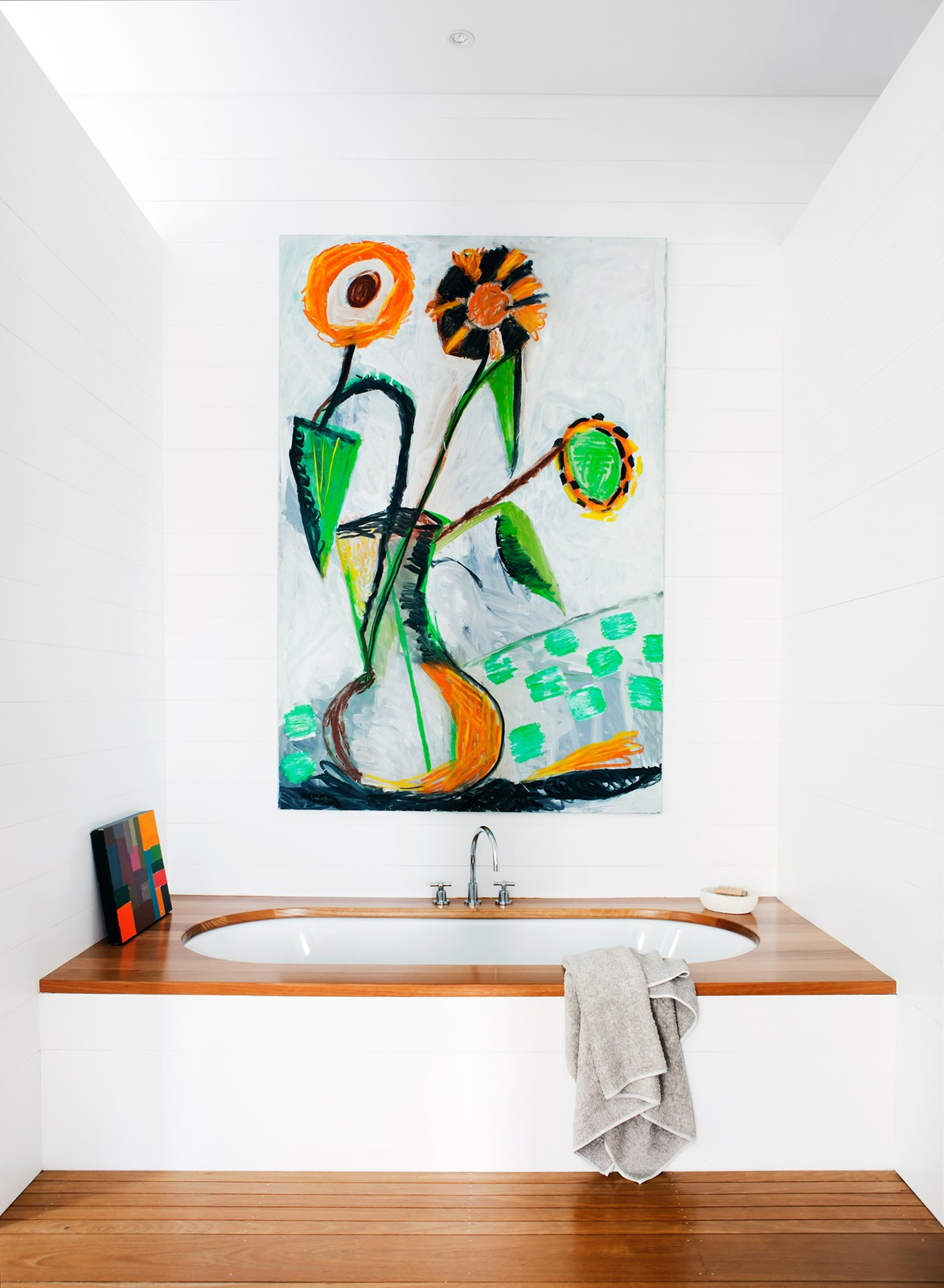 "Topped with black-butt timber, this bath in a [semi-detached Sydney home](https://www.homestolove.com.au/sydney-semi-opens-up-to-the-elements-3388|target=""_blank"") offers the perfect place to ponder. A large-scale artwork brings another layer of personality into the space. *Photo: Maree Homer / Story: Australian House & Garden*"