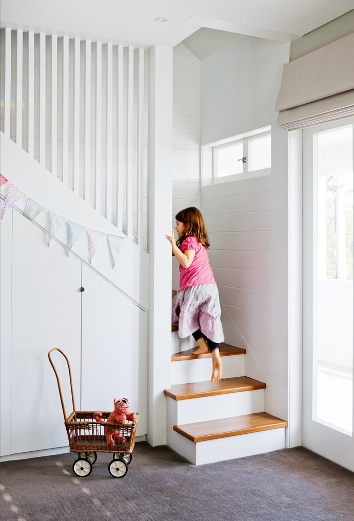 Jane's youngest daughter climbs the stairs to the new playroom in the attic. The space under the stairs has been re-purposed as storage.