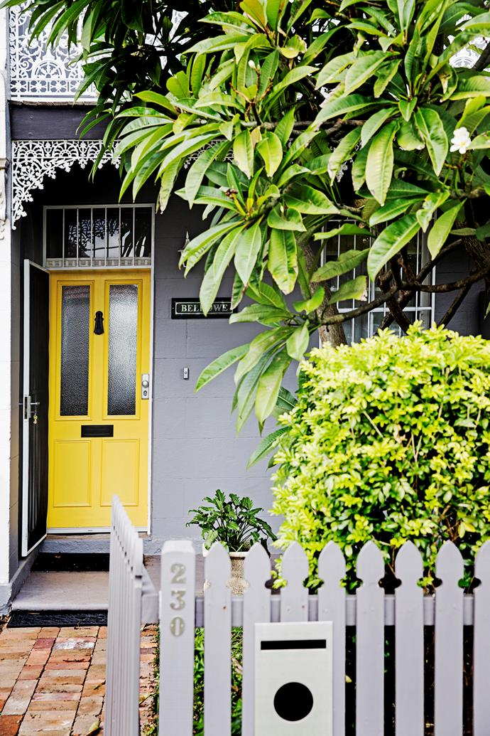 The yellow front door matches the frangipani plant.