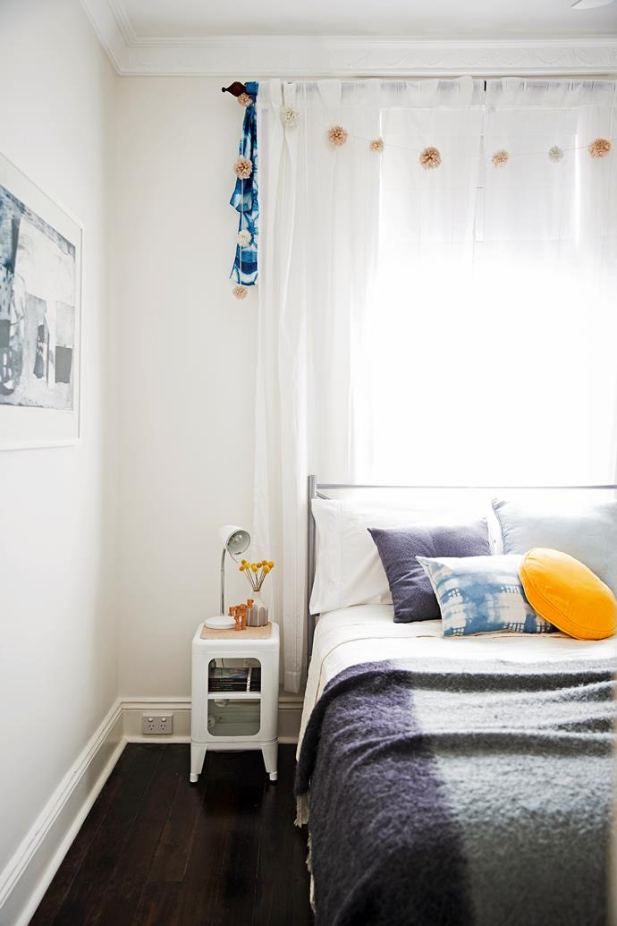 Blue-hued bedlinen, cushions and a handmade scarf set a moody scene in the second bedroom.