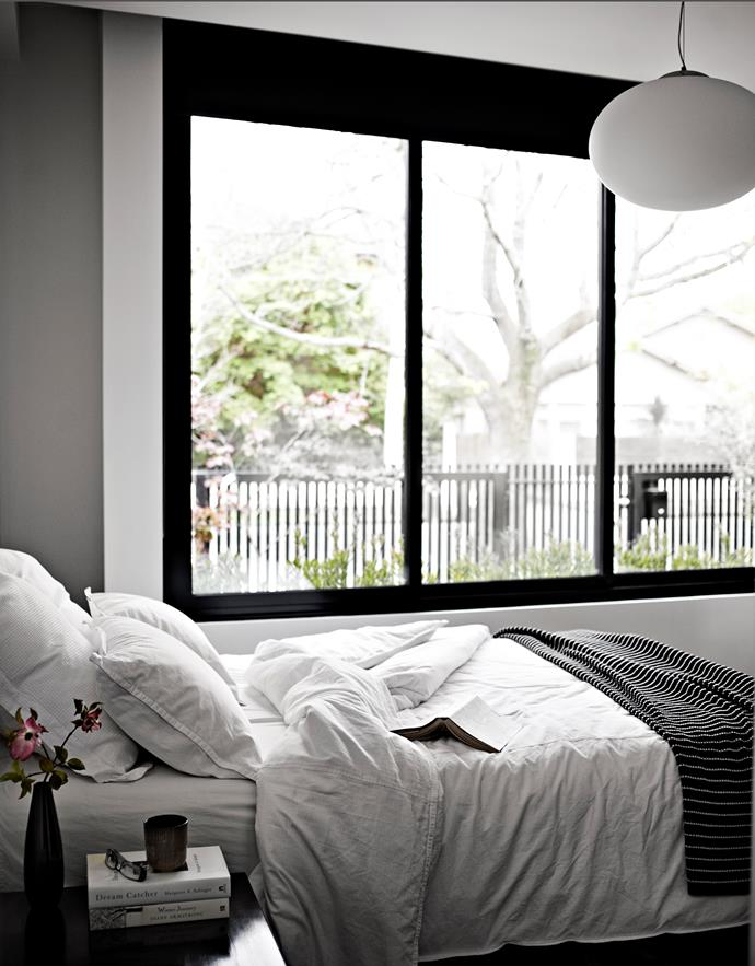The guest bedroom looks out onto the front garden. Simple white and black bedlinen suits the palette of the rest of the home.