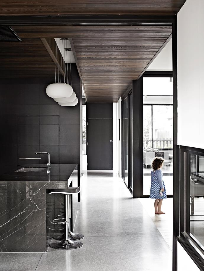 "The kitchen wall features Inalco ""Slimmker"" tiles in Black, which inspired the home's palette – and are repeated on the fireplace wall (opposite). Young Olivia looks towards the internal courtyard."
