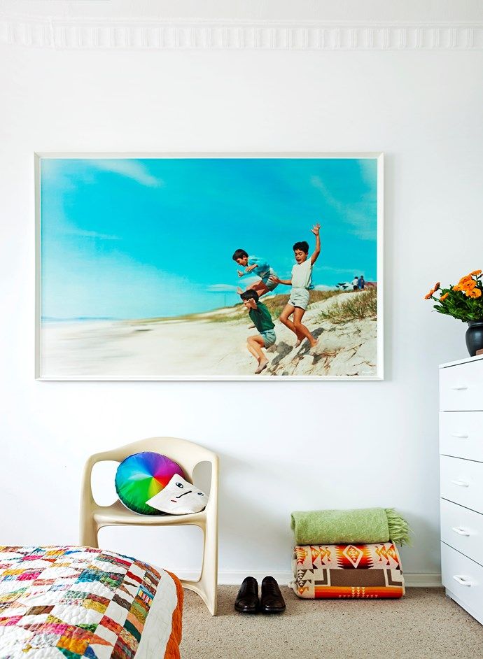 """The rainbow-coloured Inventory Studio """"Crash Pad"""" cushion was a gift from friends and works back with the blue in Murray's artwork Dunes, which hangs above."""