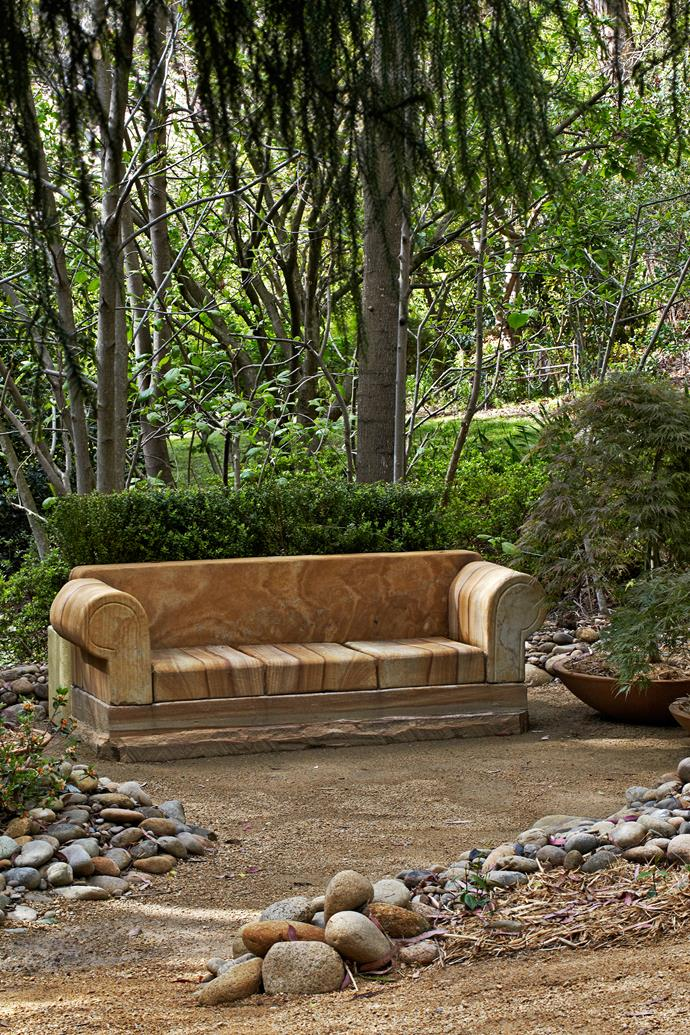 The sandstone sofa is flanked by large pots of dissected weeping maple 'Inaba Shidare'.