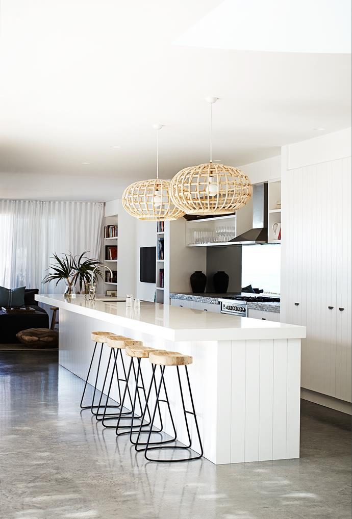 "Cane pendants and timber panelled kitchen cabinetry gives the kitchen of [this Sydney weatherboard home](http://www.homestolove.com.au/weatherboard-home-with-wow-factor-3458|target=""_blank"") a beachy feel. *Photo: Sharyn Cairns*"
