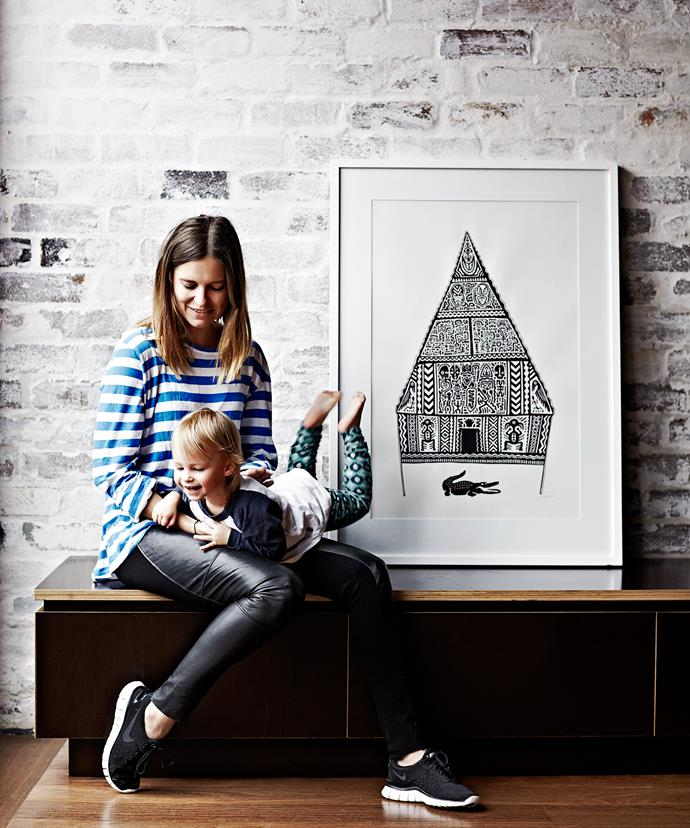 Homeowner Georgie Watts and daughter Kinga play in the kitchen area, which features recycled hardwood floors, contrasting with polished concrete floors downstairs. The print, by Melbourne artist Fred Fowler (Fred-fowler.com), was a 30th-birthday gift from Georgie's brother and sister-in-law.