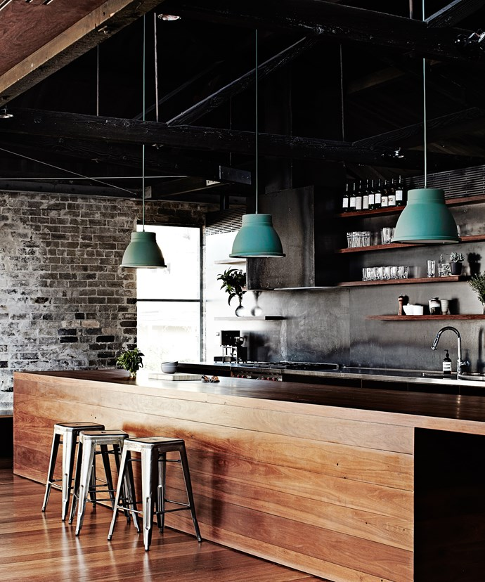 """A large island bench encourages friends and family to congregate in this kitchen. The warm timber finish offsets the exposed brick and, combined with the pendant lights and stools, gives the home an industrial vibe. Take a tour of [Merrick Watts' stylish warehouse home](http://www.homestolove.com.au/inside-comedian-merrick-watts-happy-home-3465