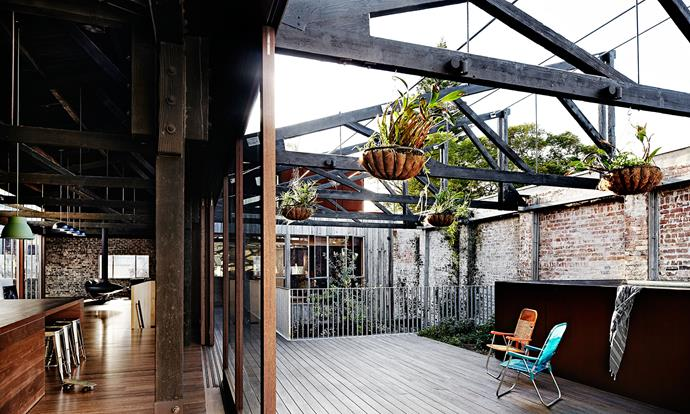"""Large, sliding glass doors with ironbark frames open the length of the deck, allowing the house to """"breathe"""", creating the perfect indoor-outdoor space. The house is constructed from bricks, concrete, steel and timber."""