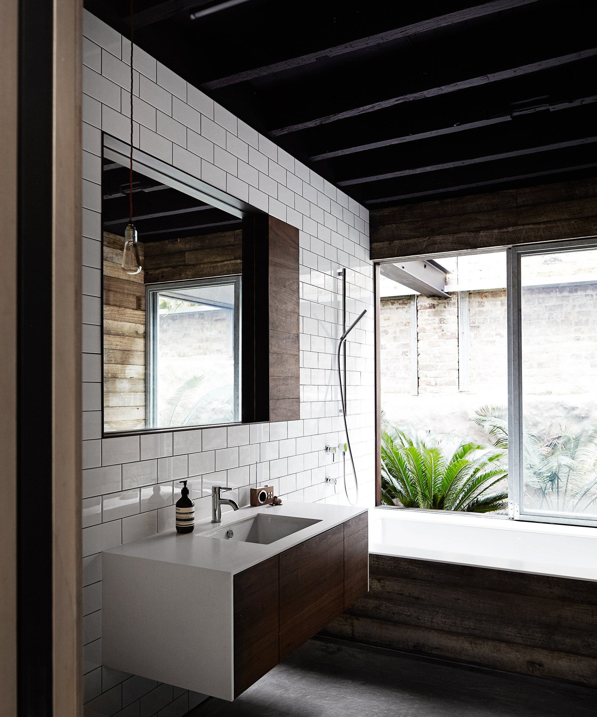 A mix of materials including subway tiles, reclaimed wood and glass, ties in with the overall design concept of this [sleek warehouse conversion](http://www.homestolove.com.au/inside-comedian-merrick-watts-happy-home-3465). Photo: Sharyn Cairns
