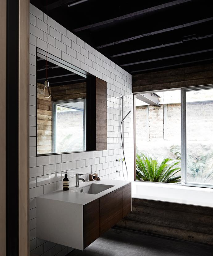In the bathroom, a mix of materials including subway tiles, reclaimed wood, glass and a single bulb pendant ensure the look is in keeping with the overall design concept.