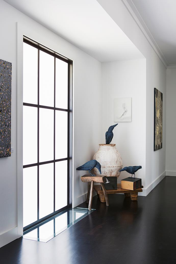 """The wide corridor serves as gallery space. Pot, [Ottoman Empire](http://www.ottomanempire.com.au/?utm_campaign=supplier/ target=""""_blank""""). Stool, [Lauder & Howard](http://lauderandhoward.com/?utm_campaign=supplier/ target=""""_blank""""). Crow figures, [Mossenson Galleries](http://mossensongalleries.com.au/?utm_campaign=supplier/ target=""""_blank""""). Paul Uhlmann artwork (above crows), [Art Collective WA](http://www.artcollectivewa.com.au/?utm_campaign=supplier/ target=""""_blank"""")."""