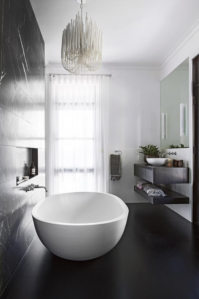 """A feature wall of Pietra Grigio marble tiles from [Bernini Stone & Tiles](http://www.bernini.com.au/?utm_campaign=supplier/ target=""""_blank"""") injects dark drama. Apaiser bath and basin, [Rogerseller](http://www.rogerseller.com.au/?utm_campaign=supplier/ target=""""_blank""""). Tapware, [Reece](http://www.reece.com.au/?utm_campaign=supplier/ target=""""_blank""""). Striped towel, [Ottoman Hamam](http://ottomanhamam.com.au/ target=""""_blank""""). Pendant light, [Blu Peter](http://www.blupeter.com.au/?utm_campaign=supplier/ target=""""_blank"""")."""