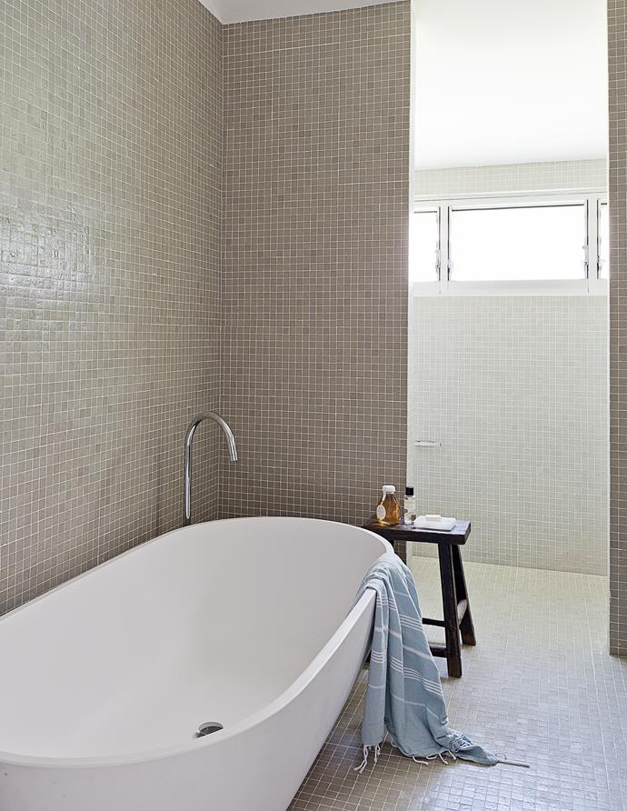 A Vizzini bath from Renovation Boys is the centrepiece in the bathroom, finished in glass mosaic tiles from Artedomus.