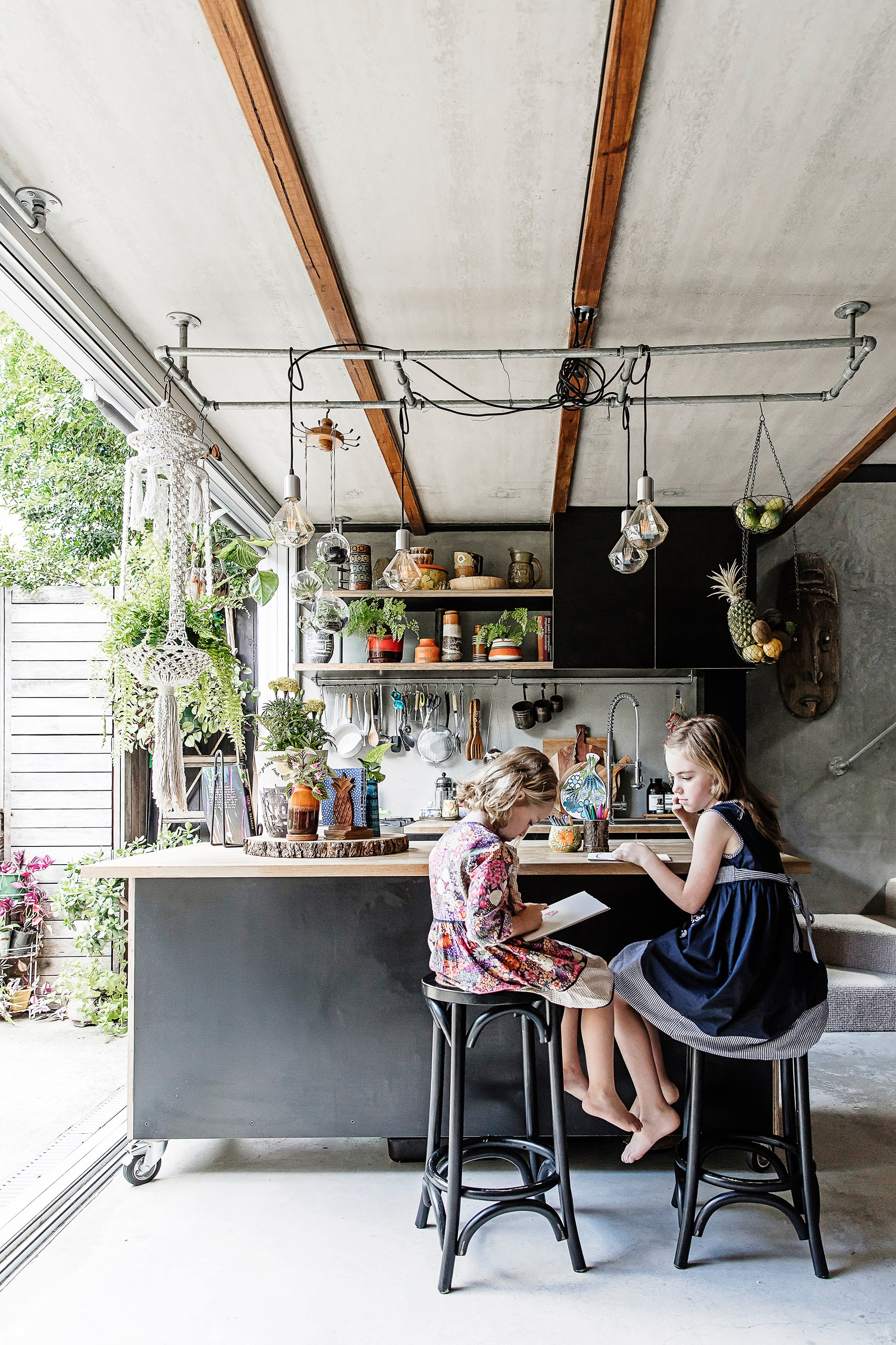 """Another favourite place to hang for Mila and her sister Rose is at the kitchen bench of this [concrete jungle home](http://www.homestolove.com.au/concrete-jungle-step-inside-the-ultimate-urban-oasis-3487