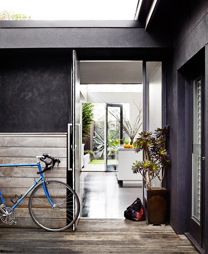 An oversized and customised floor-to ceiling, two-way entrance door hints at the generous feel of this home. Timber slats, a continuation of the spotted gum decking, hide garbage bins, as well as Hugo the dog's sleeping quarters – the area doubles as a kennel.