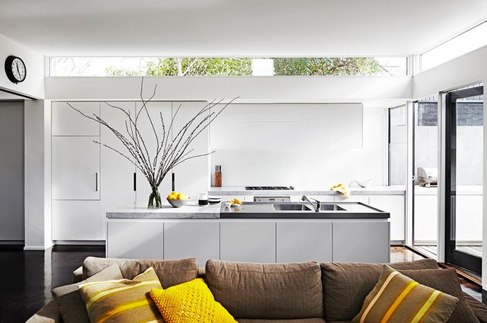 """The joinery in the kitchen is a sophisticated design, requiring no handles. The couple particularly love the island bench with its deep, stainless-steel sinks and the flush-mounted Smeg cooktop. Above the stove is a fold-out flap for the Qasair exhaust system. """"It's as close to a restaurant exhaust as you will get,"""" Denis says."""