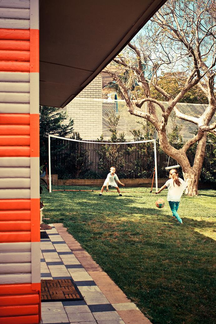 Ruby and Frankie enjoy a game of footie in the garden of their renovated family home in Sydney. Parents Priscilla and Nick had to put the high fence net up to save the neighbours' windows!