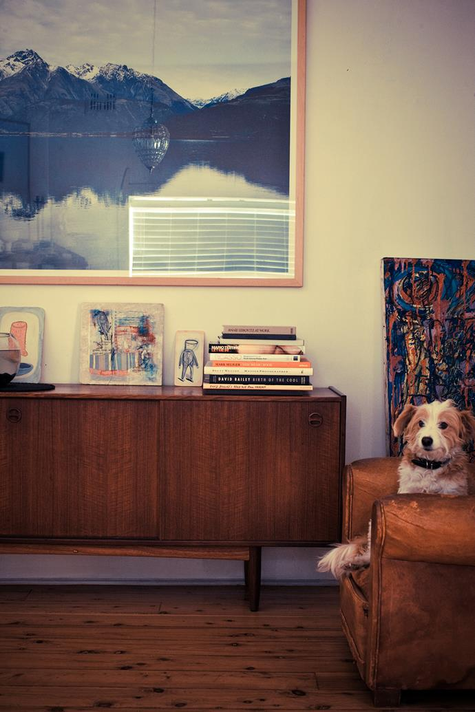 Mikey the pooch enjoys a rare moment on the leather armchair in the lounge room. Priscilla bought the retro sideboard from eBay several years ago. The photograph is another of Nick's own, an outtake from a shoot in Queenstown, New Zealand.