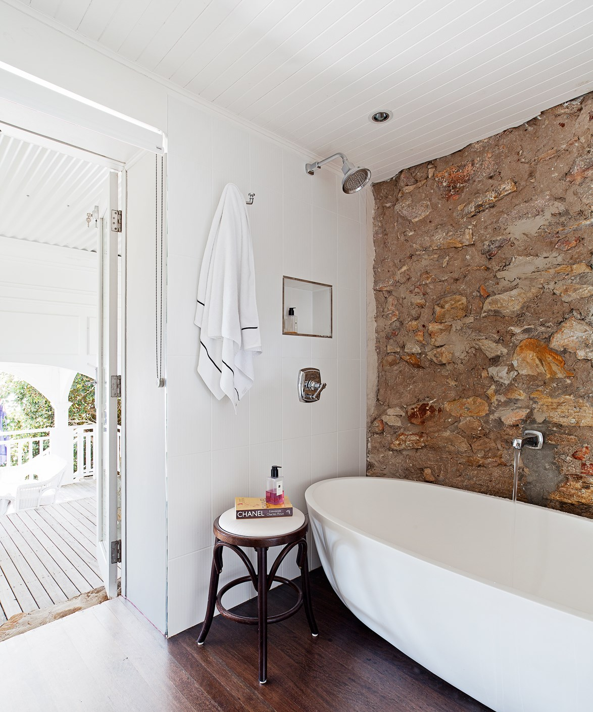 "The bathroom in this [Hamptons style home](https://www.homestolove.com.au/how-to-get-the-hamptons-look-3523|target=""_blank"") expertly pairs a modern bath tub against an exposed sandstone wall."
