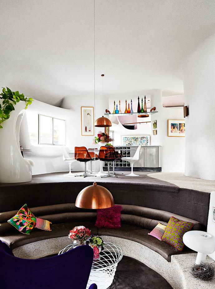 The multilevel house makes the most of the sloping site. The artwork, left of table, is by Irene Ferguson. Nancy bought the original set of 1970s copper Lucite swivel chairs online.
