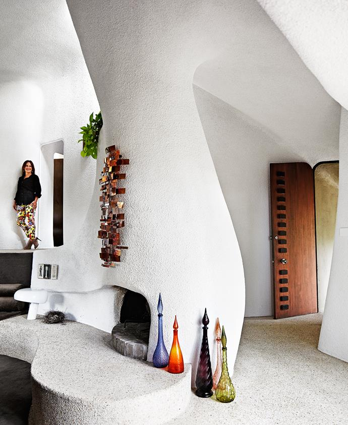 """A 1969 Curtis Jeré installation hugs the fireplace and echoes the original front door, which was repainted in Porter's Paints """"Rich Copper"""". Nancy restored copper fittings throughout the home, which previous owners had removed. A collection of genie bottles, from eBay, combine a sense of fantasy with 1970s pizzazz."""