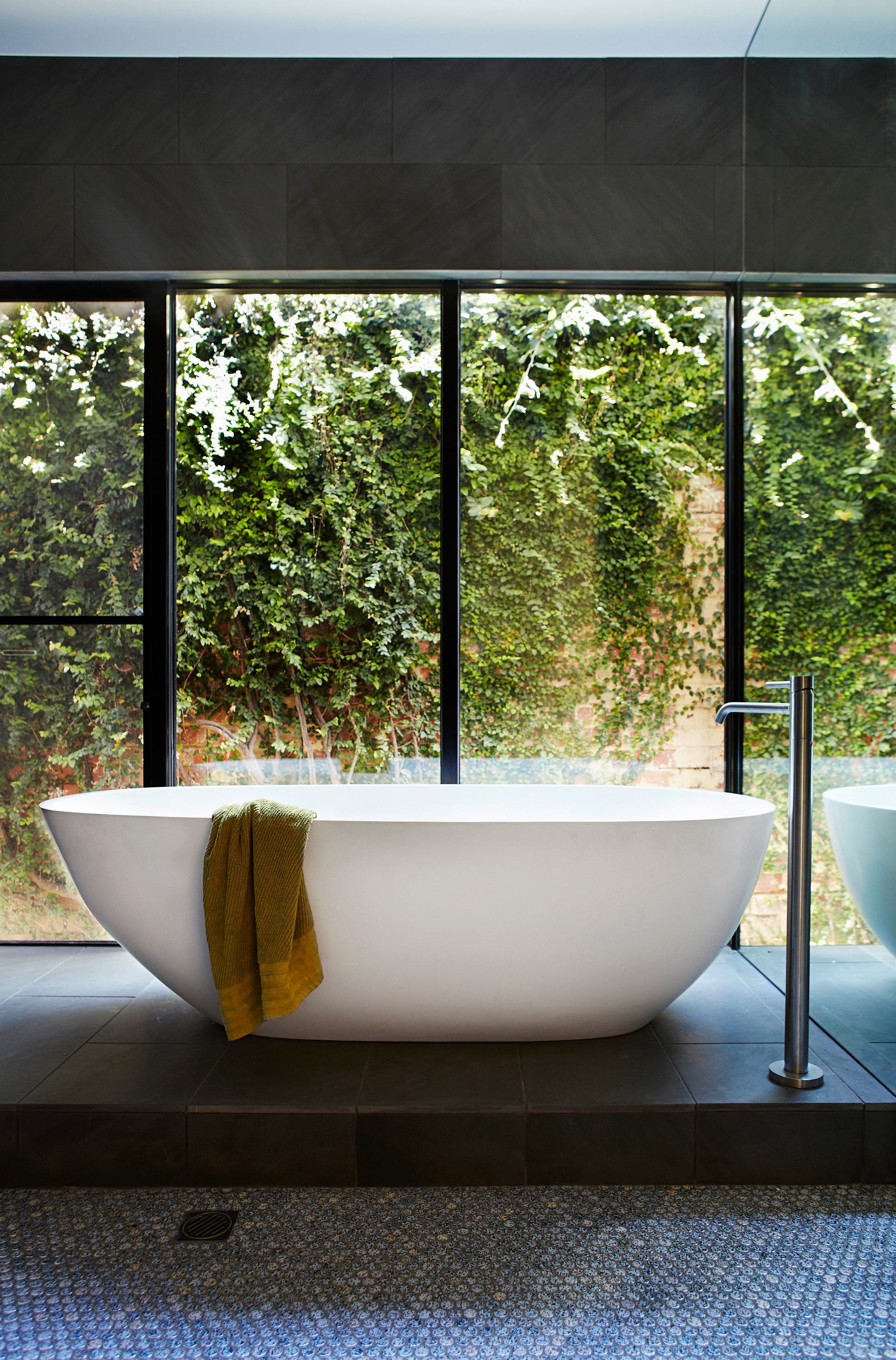 """A verdant view can be enjoyed from this freestanding bath within the parents' retreat of a [heritage home in Melbourne](http://www.homestolove.com.au/heritage-home-gets-a-colourful-update-3541