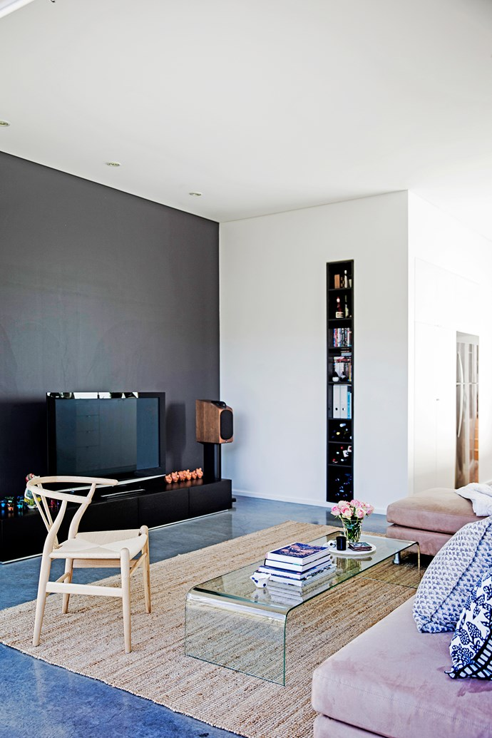 """A clever solution to hiding your entertainment unit or television is to have it blend into the background. If you have white or light-coloured walls, a dark feature wall will do the trick. Here, [Porter's Paints](http://www.porterspaints.com/?utm_campaign=supplier/