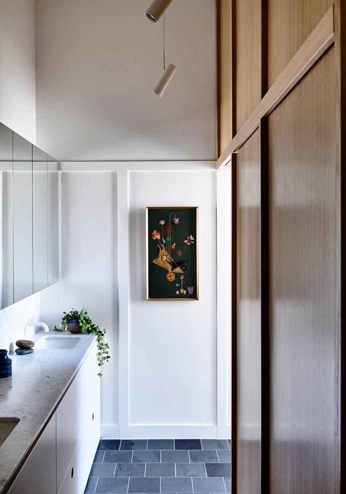 The family-friendly bathroom also has a laundry concealed behind timber joinery.
