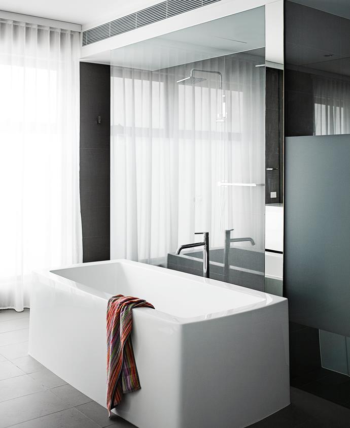 "Sheer curtains also feature in the master bedroom's ensuite for the sense of ""cosiness"" they add. The bath came from Choice Bathrooms and the grey floor tiles from National Tiles. The toilet is concealed behind a partly frosted glass door."