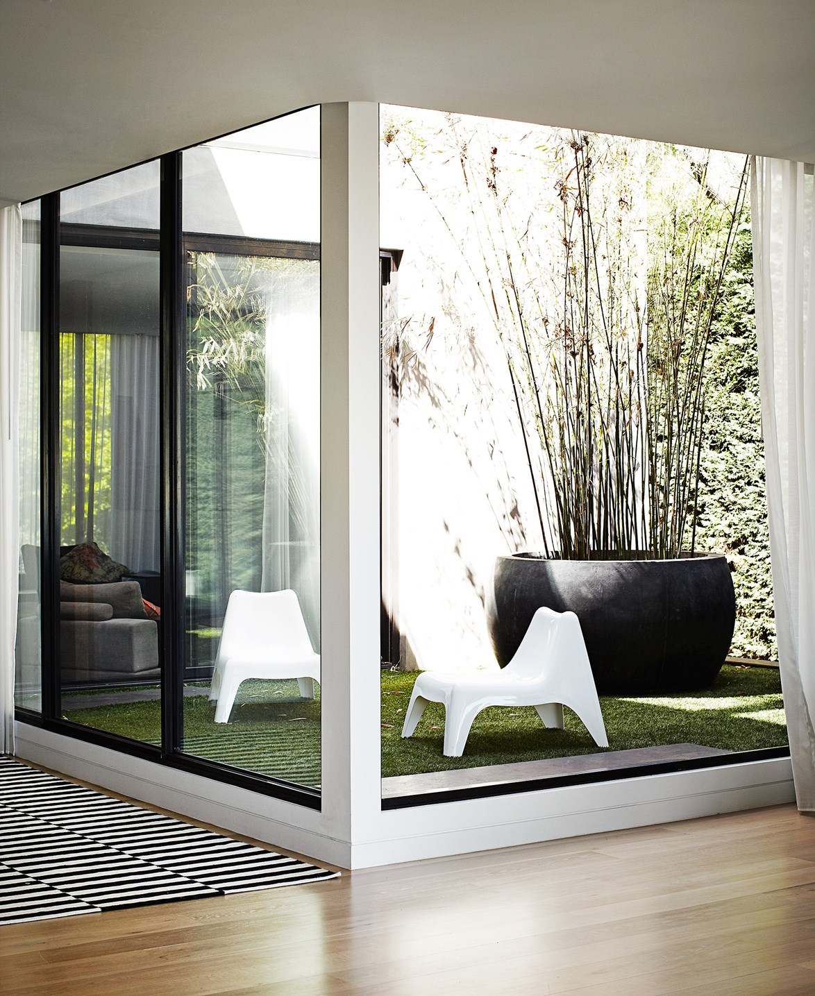 "A pair of white Ikea chairs create a focal point in this internal courtyard – and provide seating for the homeowner Tracy, who often reads out there. ""There is no lawn mowing or gardening in that area except for watering the bamboo,"" Tracy says of her garden area, faking it with artificial grass for the perfect low-maintenance space."