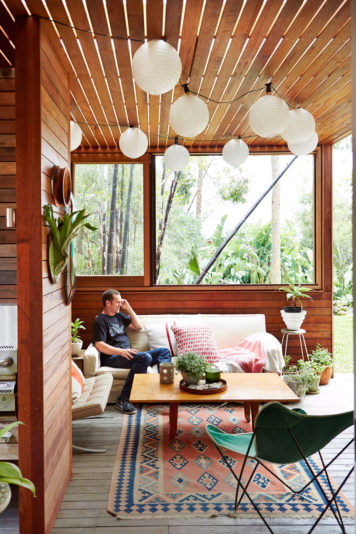 Clusters of plants, a patterned rug and comfy day bed make this the ultimate outdoor area. Photo: John Paul Urizar / *bauersyndication.com.au*