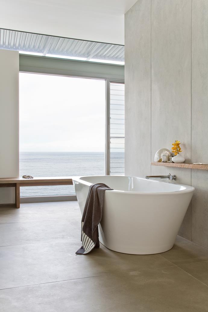 """""""This bathroom has strong natural light and the raw look of the wall panels works really well with the glass and timber,"""" says Steven, one of the architects who designed the house."""