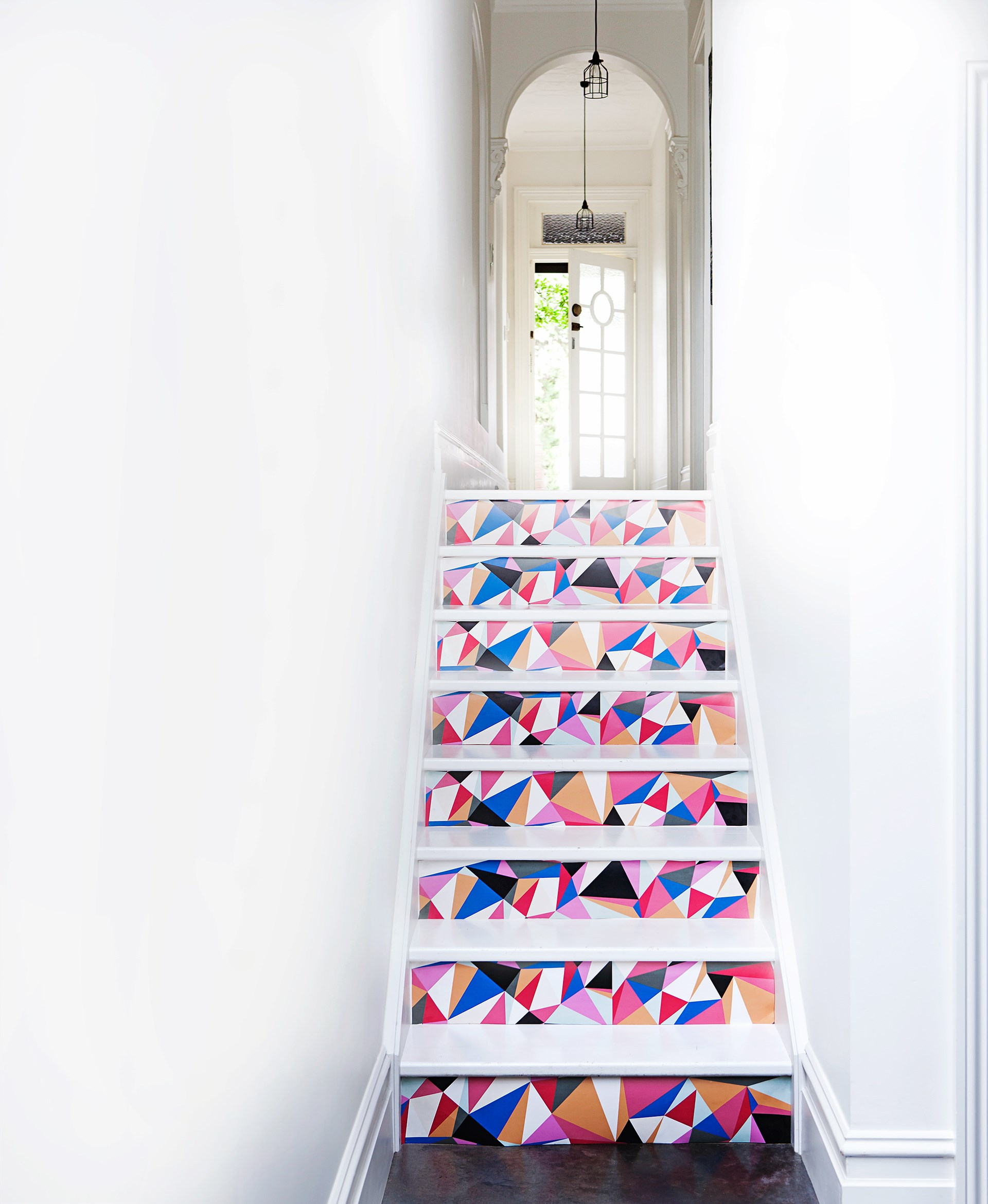 """Graphic wallpaper with hint of pink adds instant flair to the entry hall of this [Sydney worker's cottage](http://www.homestolove.com.au/decorating-with-white-sydney-workers-cottage-reno-3576