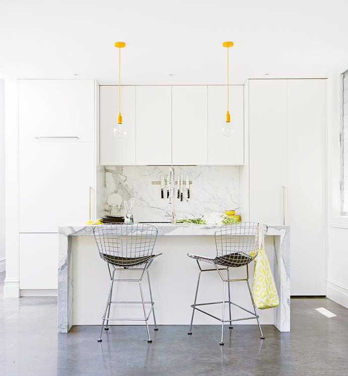 "The feeling of space in this small kitchen is enhanced with an all-white palette. The yellow pendants and the marble island bench add visual interest to the room. Take a tour of this [renovated worker's cottage](http://www.homestolove.com.au/decorating-with-white-sydney-workers-cottage-reno-3576|target=""_blank""). *Photo: Maree Homer*"