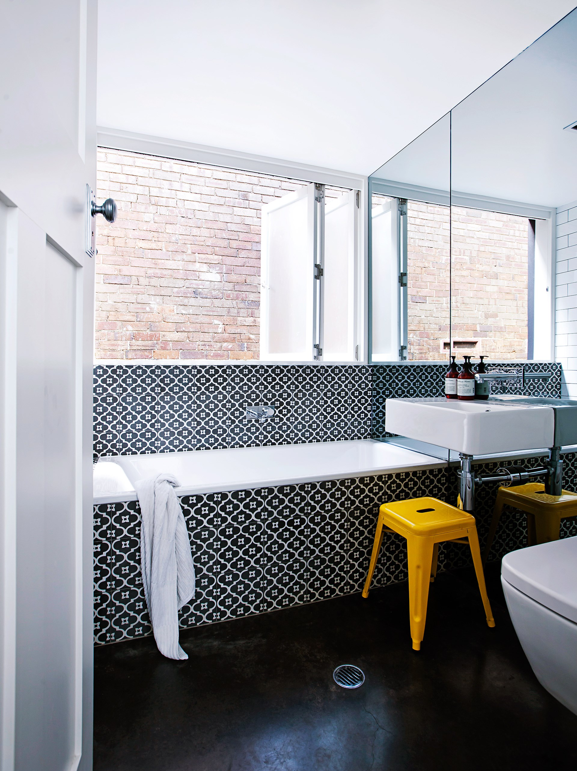 This bold bathroom contrasts with the all-white interior of this [renovated Sydney workers cottage](http://www.homestolove.com.au/decorating-with-white-sydney-workers-cottage-reno-3576) making a statement with patterned tiles, a dark floor and a striking floor-to-ceiling mirror. Photo: Maree Homer