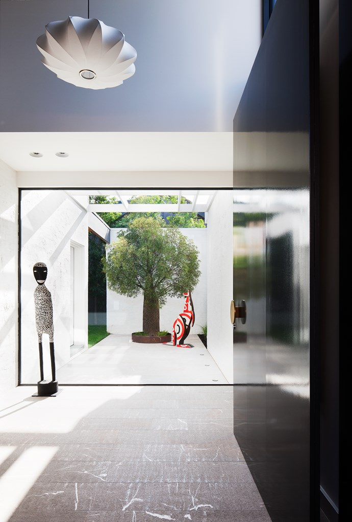 Accessed from the side, an oversized pivot door opens up into a floodlit, double-height, granite-lined entry.