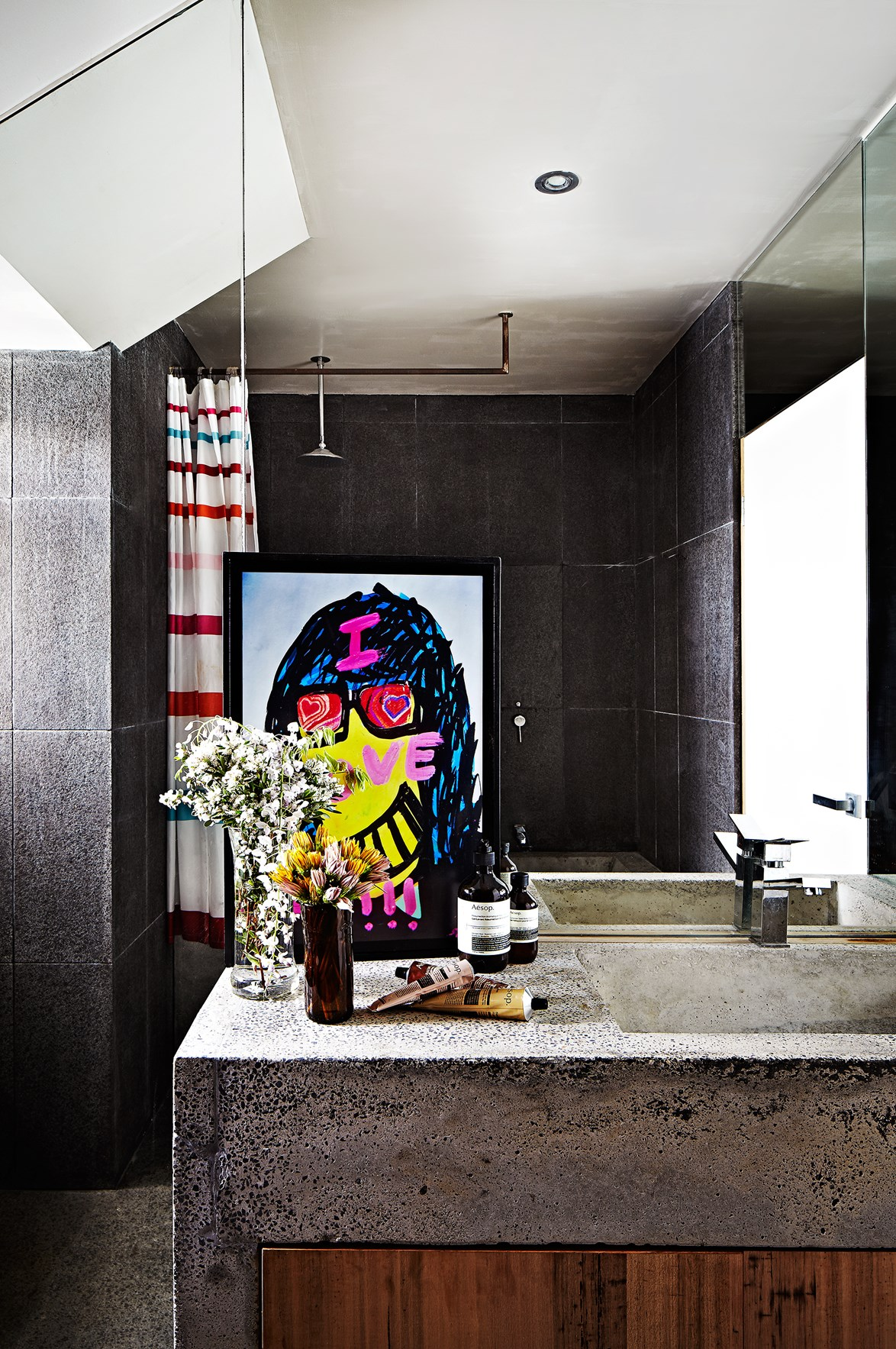 Too much concrete can sometimes feel cold and harsh but not in this bathroom. Softened with timber and bold artwork, this concrete-clad bathroom gives off an edgy, industrial vibe. Photo: Armelle Habib / *real living*