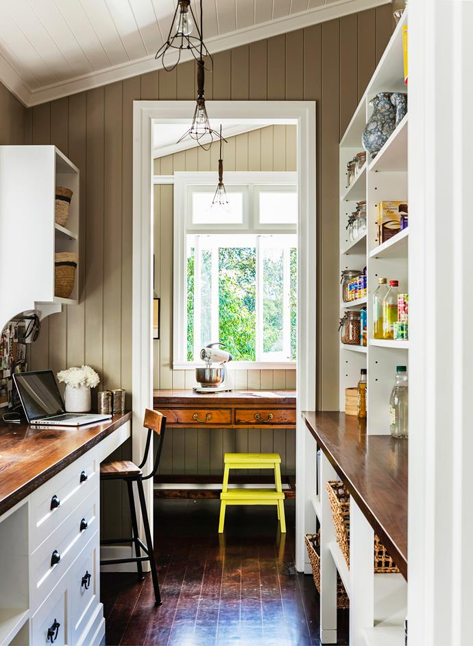 An antique railway sorting desk serves as a bench when extra workspace is needed. The benchtop in the adjacent pantry is made from roasted blackbutt.