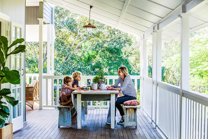 Owner Megan with two of her four boys on the upstairs verandah of their renovated 1920s Queenslander. Her decorating style is inspired by found pieces like this table and bench seats.