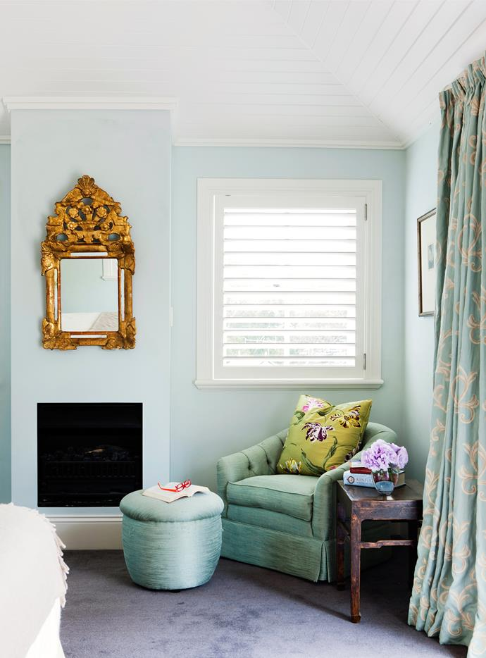 An armchair by the fire creates a cosy reading nook in the main bedroom.