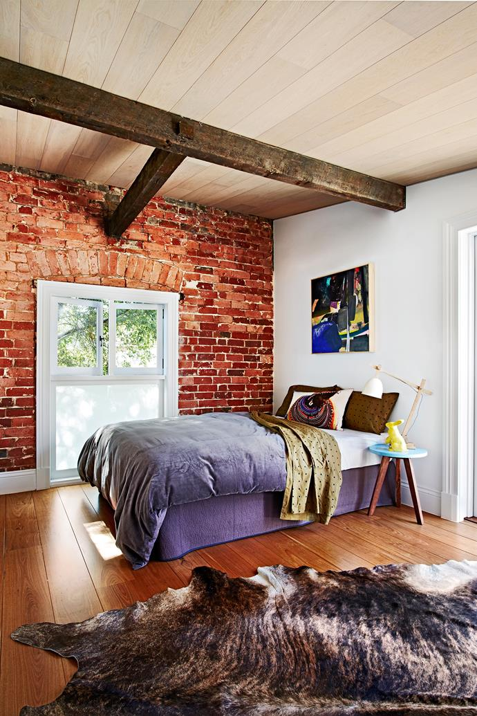 Originally horse stables, the guesthouse retains the original roof beams and brick walls. Artwork by Ali McNabney-Stevens.
