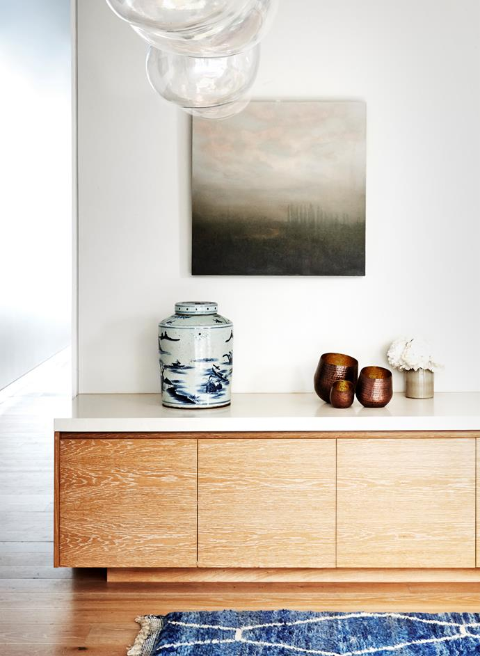 A large cabinet in the family room delivers sleek built-in storage. Artwork by Martin Campbell.