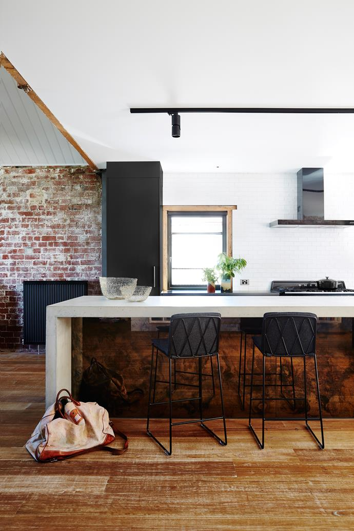 For a touch of luxe, and as the couple like to entertain, the kitchen received a concrete benchtop, which was poured onsite and wrapped in antique bronzed mirror, and a splashback made of bespoke white tiles.