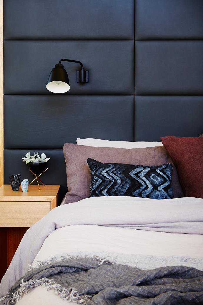 A cushy custom-made leather bedhead and linen in soft, muted tones make for a welcoming, relaxed bedroom.
