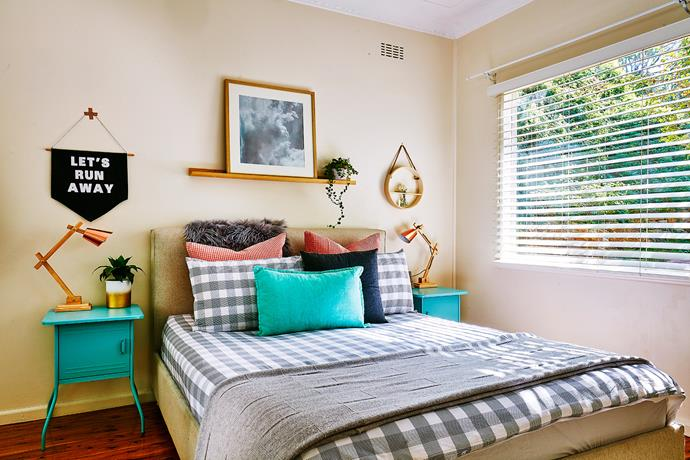 A neutral wall sets off the checked quilt cover and a colourful array of cushions.